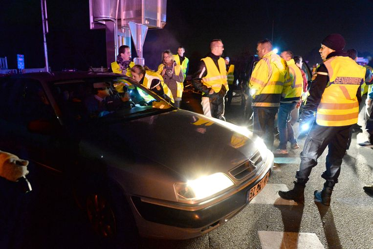 Een agente spreekt een bestuurder toe die is vast komen te zitten in een actie bij Le Mans. Beeld AFP
