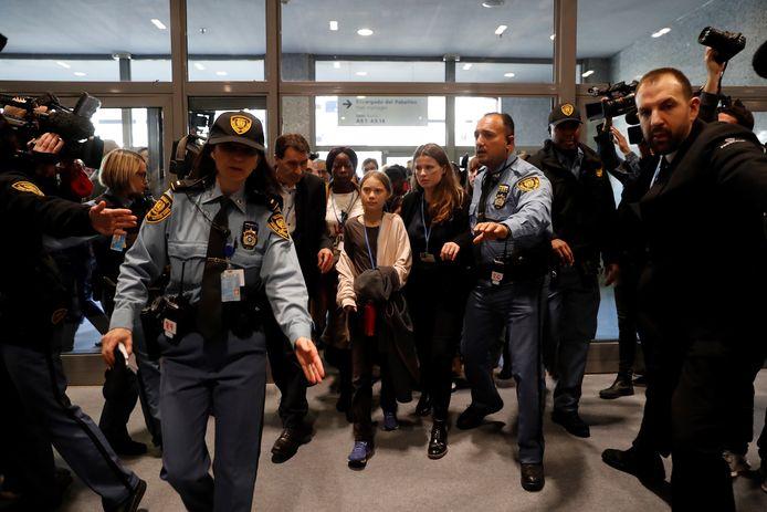 Omringd door veiligheidsbeambten van de Verenigde Naties arriveert Greta Thunberg voor haar toespraak bij de internationale klimaatconferentie COP25 waar zij de wereldleiders de wacht aanzegt. Foto EPA/JUAN CARLOS HIDALGO)