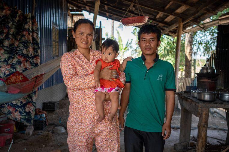 Vakbondsleider Kim Sokchan met vrouw en kind. Het stel werkte in dezelfde textielfabriek, die in september dichtging. Beeld Antoine Raab