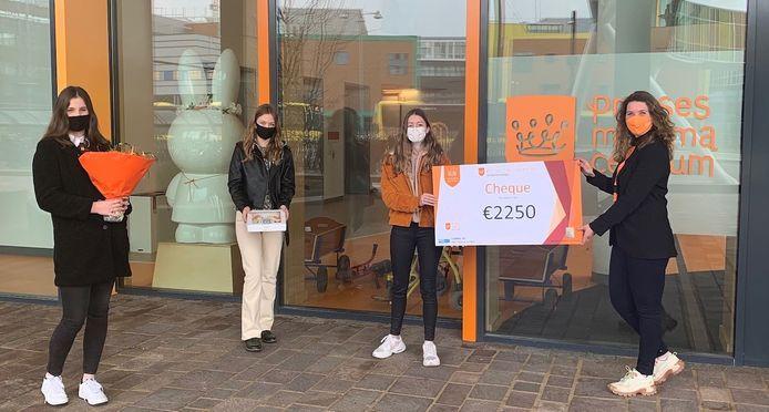 De vwo-leerlingen Vera Markvoort, Kim Sanderman en Lisanne den Hertog (vanaf links) overhandigen de cheque van 2250 euro aan Renske Fernandes van het prinses Maxima Centrum in Utrecht.