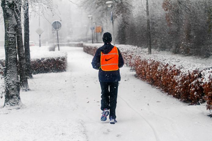 Hardloper betreedt de besneeuwde paden van de Grauwe Polder in Etten-Leur.
