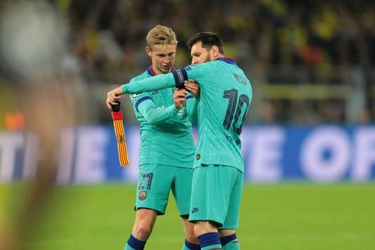 Frenkie de Jong helpt invaller Lionel Messi met de aanvoerdersband.