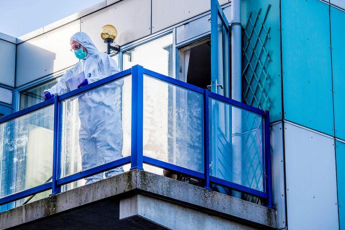 Forensisch medewerkers van de politie doen onderzoek op het balkon waar het lichaam van de pasgeboren baby werd gevonden.