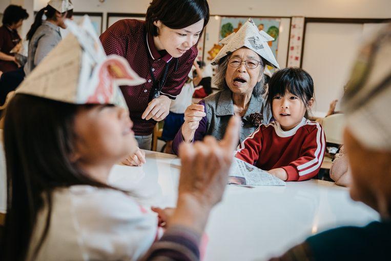Bejaarden helpen kleuters met het vouwen van papieren samoeraihelmen. Het is een van de dagelijkse gezamenlijke activiteiten.  Beeld Jun Michael Park/laif