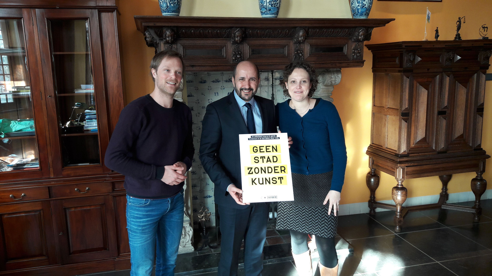 Burgemeester Marcouch (m) neemt een manifest met aanbevelingen voor de kunst in ontvangst van Joram Kraaijeveld (l) en Lene Grooten (r).