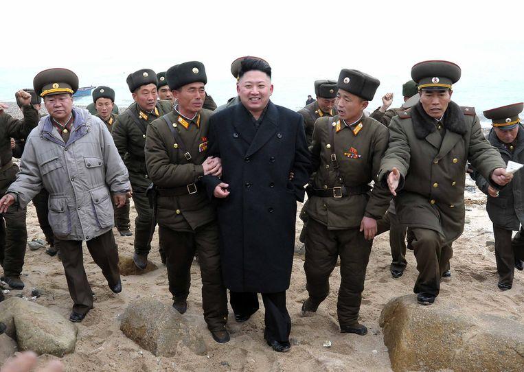 De Noord-Koreaanse leider Kim Jong-un omringd door militair personeel. Beeld ap