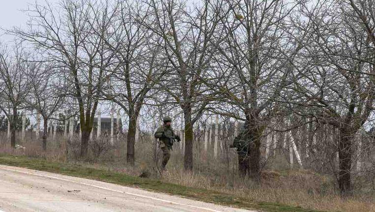 Gewapende mannen staan langs de weg naar de luchthaven van Simferopol, de hoofdstad van de Krim. Beeld reuters
