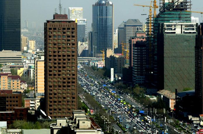 Straatbeeld van Peking. Moderne flats en kantoorgebouwen schieten als paddenstoelen uit de grond.