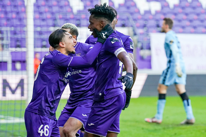 Anouar Ait El Hadj neemt het hoofd van doelpuntenmaker Albert Sambi Lokonga vast uit dolle euforie. Beeld Photo News
