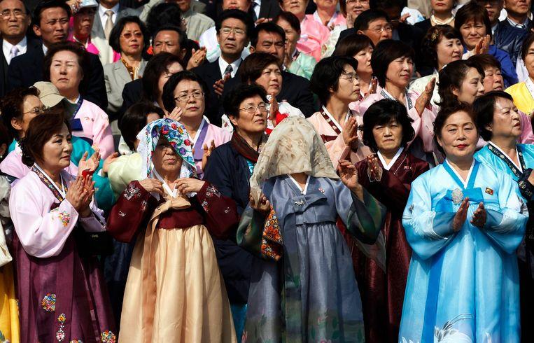 Noord-Koreaanse vrouwen wonen een militaire parade bij in 2012. Sommigen beschermen zich tegen de zon met een zakdoek over hun hoofd.  Beeld REUTERS