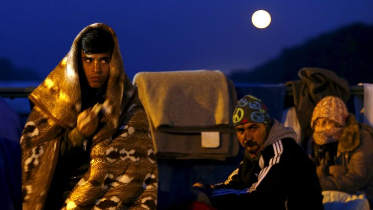 Vluchtelingen wachten op een brug nabij Passau Beeld reuters