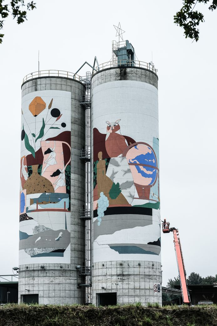 Street-art kunstenaar Robin Nas aan het werk bij de silo's van het steengroevebedrijf Sibelco in Winterswijk.