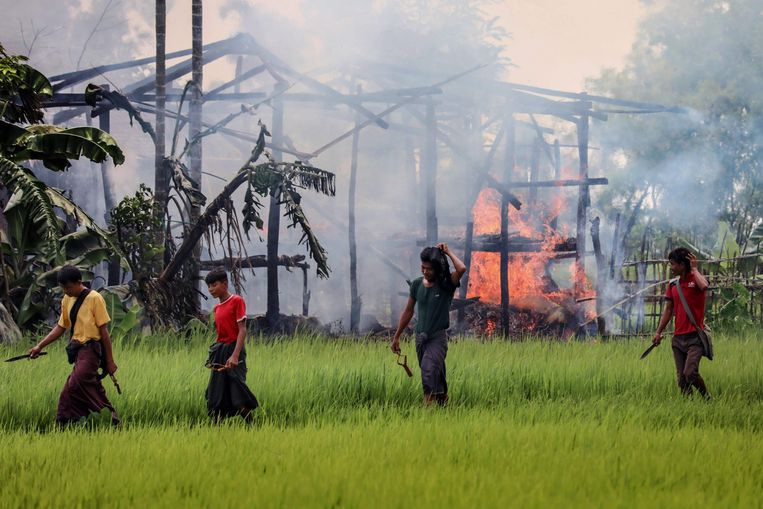 Mannen gewapend met messen en katapulten passeren in september 2017 een brandend huis in de Myanmarese deelstaat Rakhine. Beeld AFP