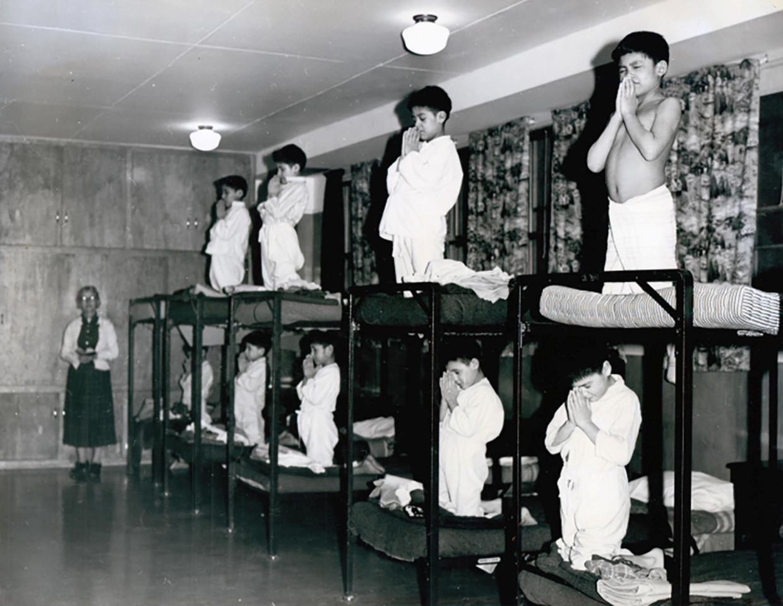 Jongens bidden op hun slaapkamerzaal in de Bishop Horden Memorial School, een internaat vaar veel van de Cree gemeenschap heen werden gestuurd in Ontario, Canada. Foto dateert uit 1950.  Beeld Shingwauk Residential Schools Centre via REUTERS