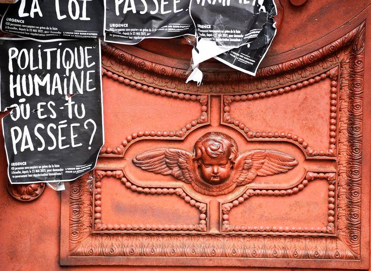 Een oproep tot 'menselijke politiek' aan de poort van de Begijnhofkerk in Brussel. Beeld Photo News
