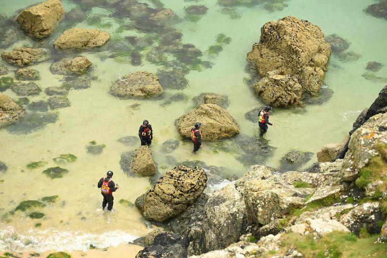 Agenten in wetsuits patrouilleren langs de rotskust bij Carbis Bay om de G7-locatie te beveiligen.  Beeld AFP