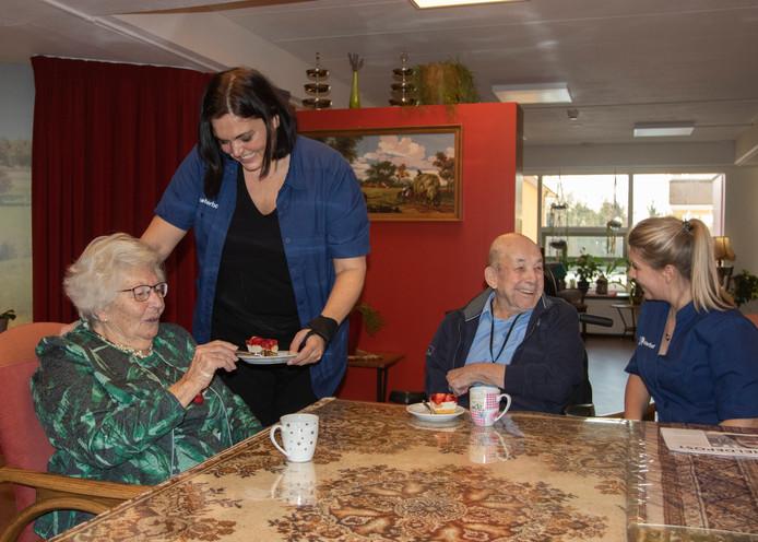 Mevrouw van de Parel krijgt koffie en een gebakje uit handen van werknemer Marloes van Eenige-Verschuure. Ook meneer Ticheler en Guusje de Smit vieren de 9 die Cederhof als aanbevelingscijfer heeft gekregen.