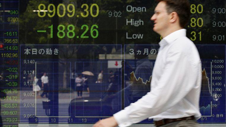 Een man op straat in Tokyo passeert dinsdag een bord met de koers van de Nikkei-index. Beeld ap