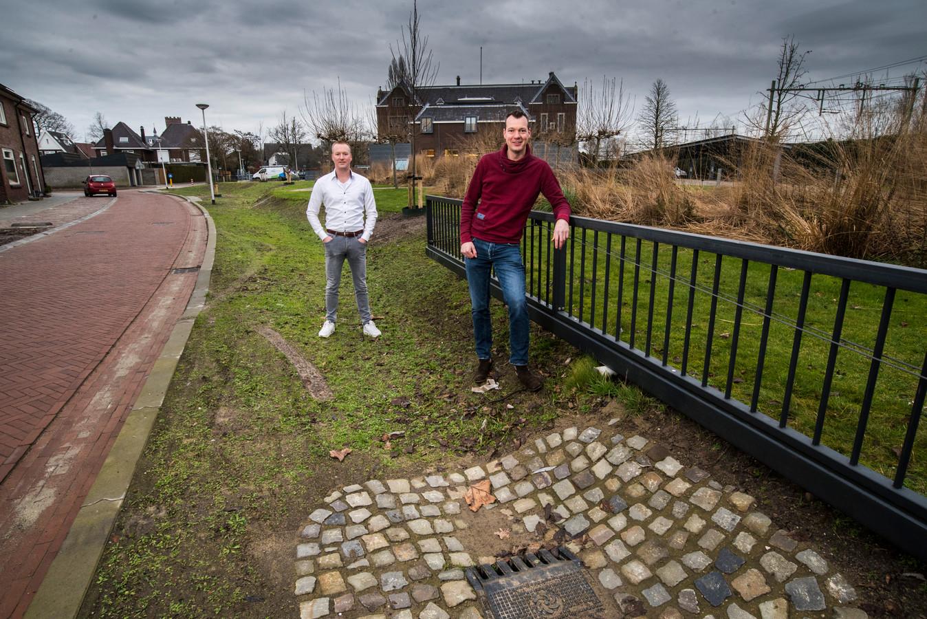Joris Sprangers (WBO Wonen ) en Jeroen Buitenweg ( gemeente Oldenzaal ) staan bij een wadi die het regenwater opvangt om verdroging grond te voorkomen.