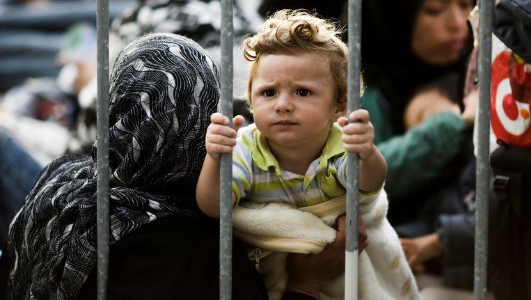 Een kind op de vlucht, achter een hek in het grensstation van Obretzje, Slovenië. Beeld AP
