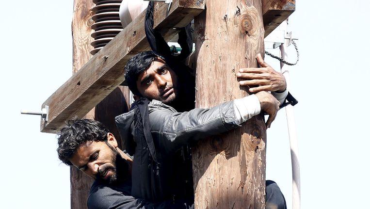 Een Pakistaanse migrant probeert zichzelf op te hangen aan een elektriciteitspaal in het registratiecentrum op Lesbos. Een andere migrant probeert hem tegen te houden. Beeld reuters