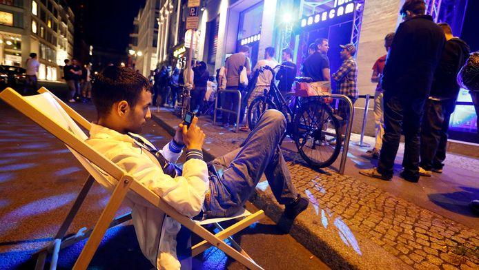 Een man wacht in een strandstoel op de nachtelijke opening van een winkel in Berlijn.