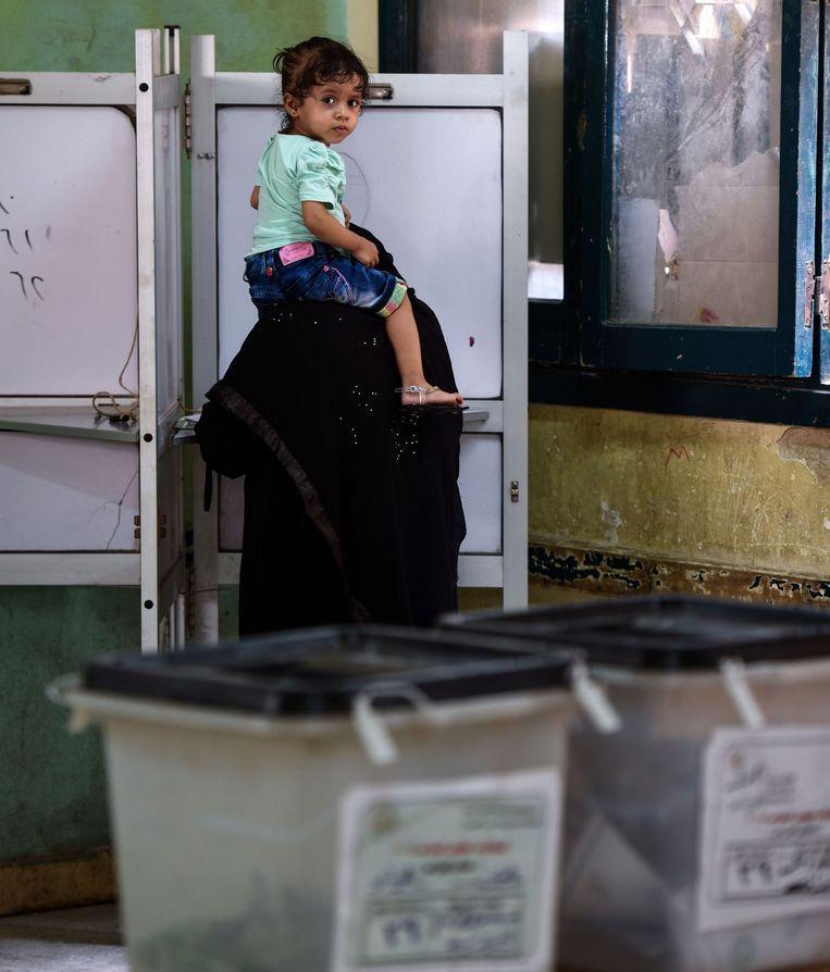 Een Egyptische vrouw brengt in Giza haar stem uit bij de parlementsverkiezingen. Beeld AFP