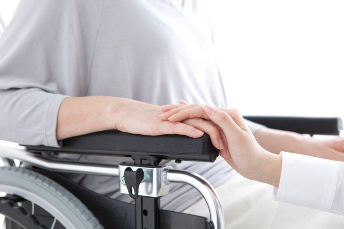 Een zorgmedewerker legt haar hand op die van een cliënt. Dit is een stockfoto en het beeld is niet geschoten in de gezinshuizen.