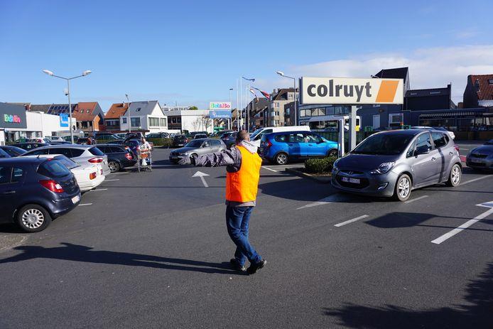 Een medewerker van Colruyt Oostende wijst toekomende klanten naar een vrije parkeerplaats. De drukte op de Torhoutsesteenweg in Oostende is groot waardoor de politie manschappen inzet om het verkeer te regelen.