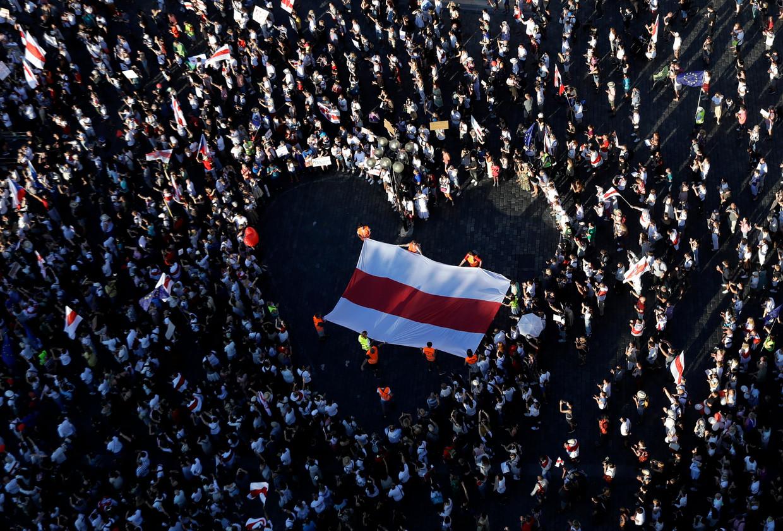 Demonstranten ontvouwen een alternatieve vlag van Wit-Rusland tijdens protesten in het centrum van Praag.  Beeld AP