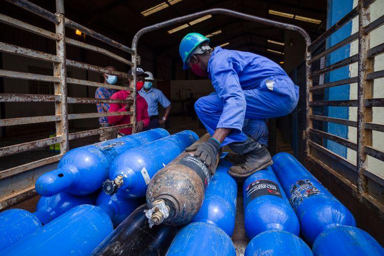 Bij een bedrijf voor golfplaten in Namanve worden zuurstofcilinders ingeladen om onder ziekenhuizen in Oeganda te verdelen. Beeld Katumba Badru