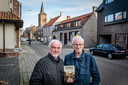 Jacques Viaene en Jean-Marie Lermyte met het boek 'De Geschiedenis van Kachtem'.  De foto is genomen op dezelfde plaats die op de cover van het boek prijkt. Op de achtergrond staat nog hetzelfde huis als toen, aan het begin van de 20ste eeuw.