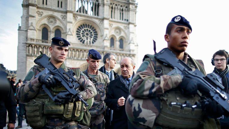 Franse soldaten worden samen met Frans Defensieminister Jean-Yves Le Drian voor de Notre Dame in Parijs. Beeld REUTERS