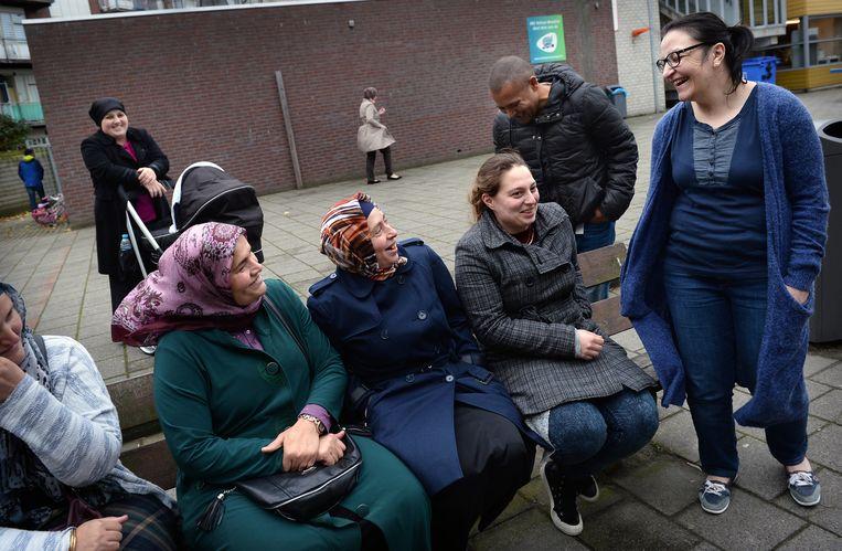 Op een basisschool in de multiculturele wijk Feijenoord in Rotterdam wachten ouders op hun kinderen. Beeld Marcel van den Bergh / de Volkskrant