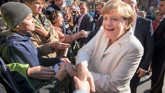 De Duitse bondskanselier Angela Merkel schudt handen na een bezoek aan een kerk.
