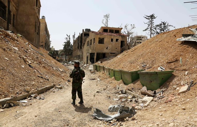 Een Syrische soldaat staat in een verwoeste straat in Douma vlak buiten Damascus. Beeld AFP