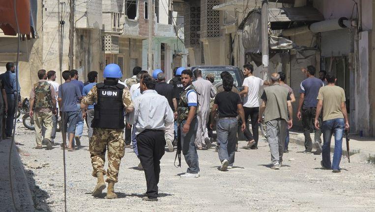VN-waarnemers bekijken de verwoeste straten van Homs. Beeld epa