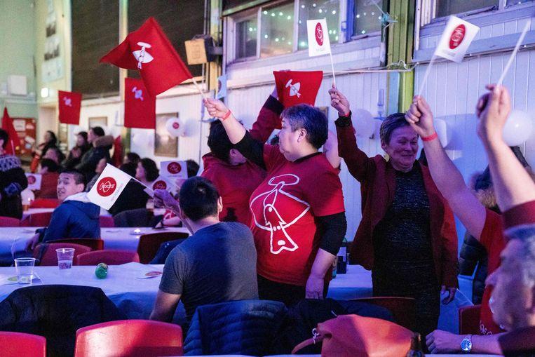 Leden van de winnende partij Inuit Ataqatigiit vieren feest als de eerste exitpolls naar buiten komen. Inmiddels heeft de partij de verkiezingen gewonnen en daarmee de mineralendelving een halt toegeroepen.  Beeld AFP