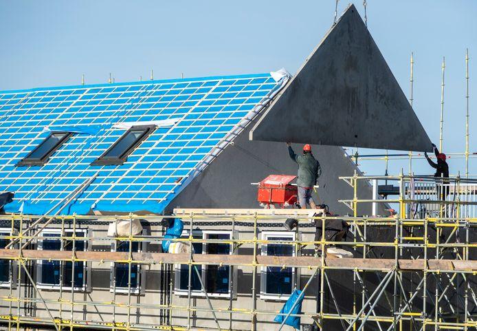 De kop van een zijgevel wordt zachtjes op zijn plek gehesen. Daarna wordt het dak er op getild en is er weer een nieuw huurhuis wind- en waterdicht in een dag tijd.