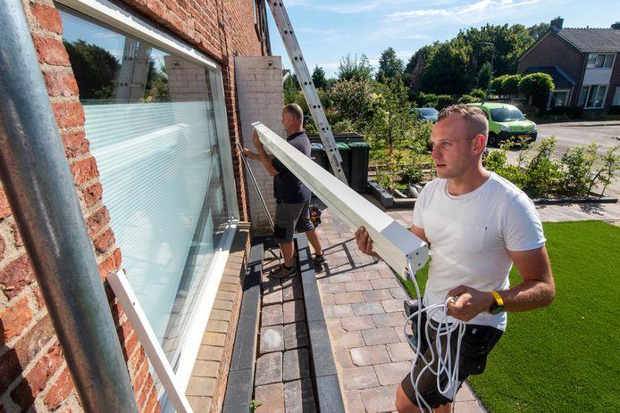 Installateurs van zonweringen zijn razend druk dit seizoen. Maurice Hoevers (witte shirt) van De Markies Zonwering met collega.