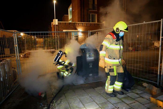 Brandweerlieden bij een brandende afvalcontainer in Zaltbommel.