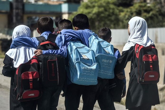 Jonge scholieren lopen langs een weg richting hun huis in Kaboel.
