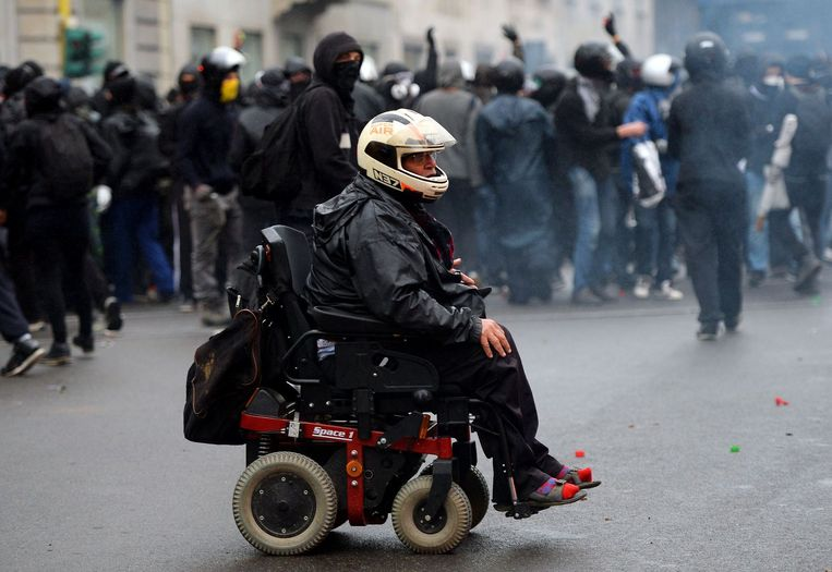 Een demonstrant in een elektrische rolstoel draagt een helm tijdens de confrontatie met de politie. Beeld anp