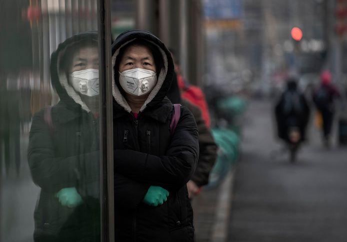 Een Chinese vrouw beschermt zich tegen het virus in Peking.