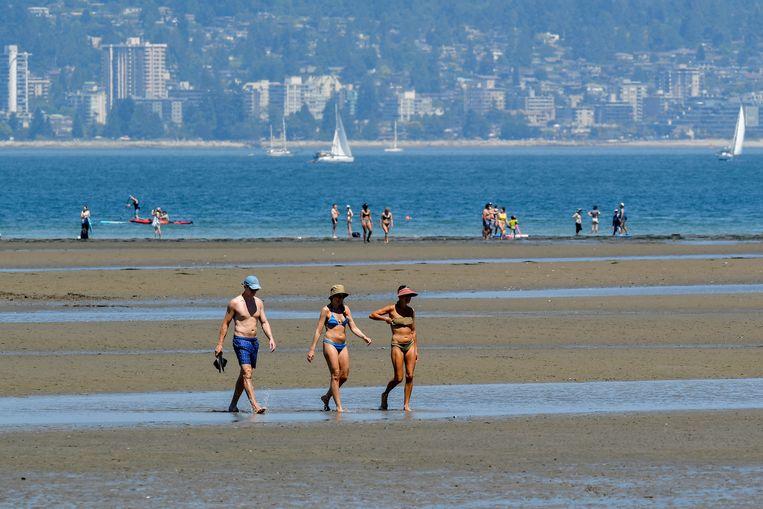 Mensen hopen wat verkoeling te vinden op het strand van Vancouver. Beeld REUTERS