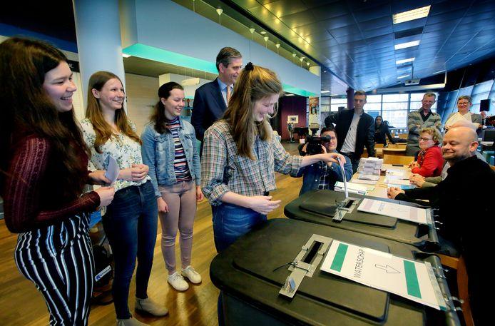 Joska, Roos, Simone en Roos uit Dordrecht mochten woensdag 20 maart voor de eerste keer stemmen. Burgemeester Wouter Kolff kijkt toe.