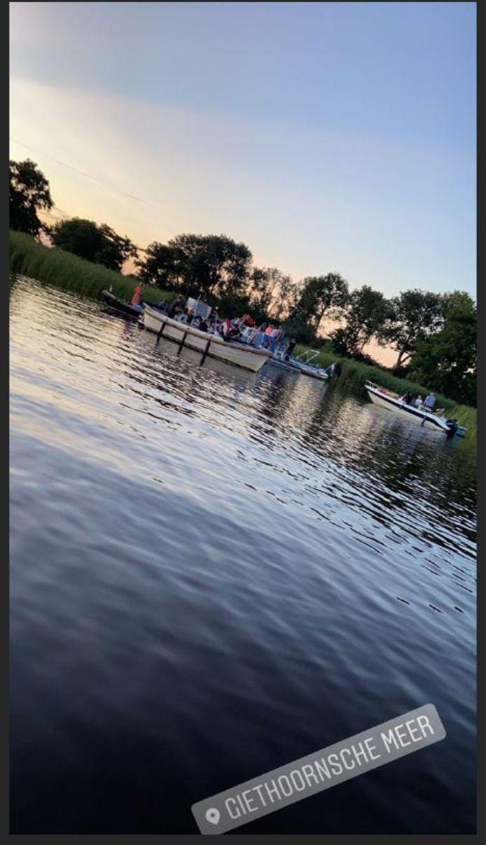Jongeren in bootjes wachten totdat het feest op het Giethoornsche meer gaat beginnen. Later op de avond volgen nog veel meer feestgangers in bootjes.