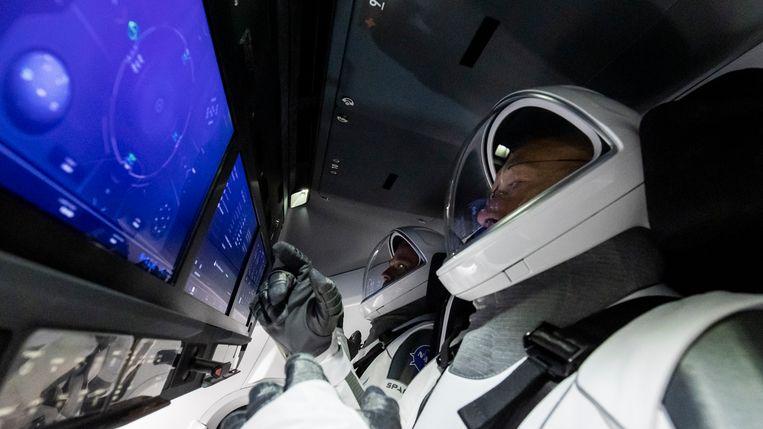 Astronauten Douglas Hurley (vooraan) en Bob Behnken trainen aan boord van de Crew Dragon. Beeld SpaceX