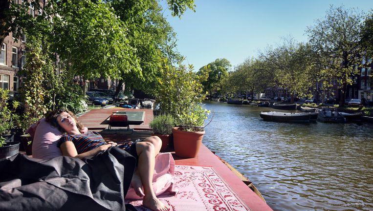 Margret Verhulst op het dek van haar woonboot aan de met veel groen beplante Marnixkade waar de parkeergarage gepland staat. Volgens de voorlopige uitslag van het referendum van West zijn er 23.160 voorstemmers. Foto Jean-Pierre Jans Beeld