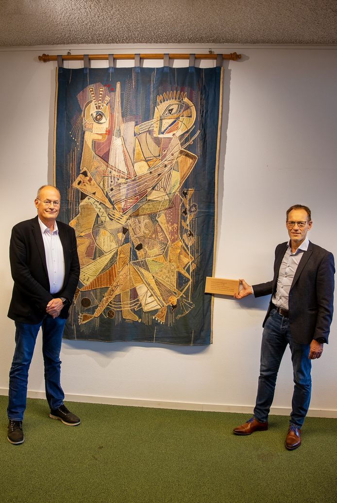 Hofnar-directeur Paul L'Herminez (links) en rector Edward de Gier van Scholengemeenschap Were Di bij het wandtapijt van Willi Martinali, dat sinds deze week in De Hofnar in Valkenswaard hangt.